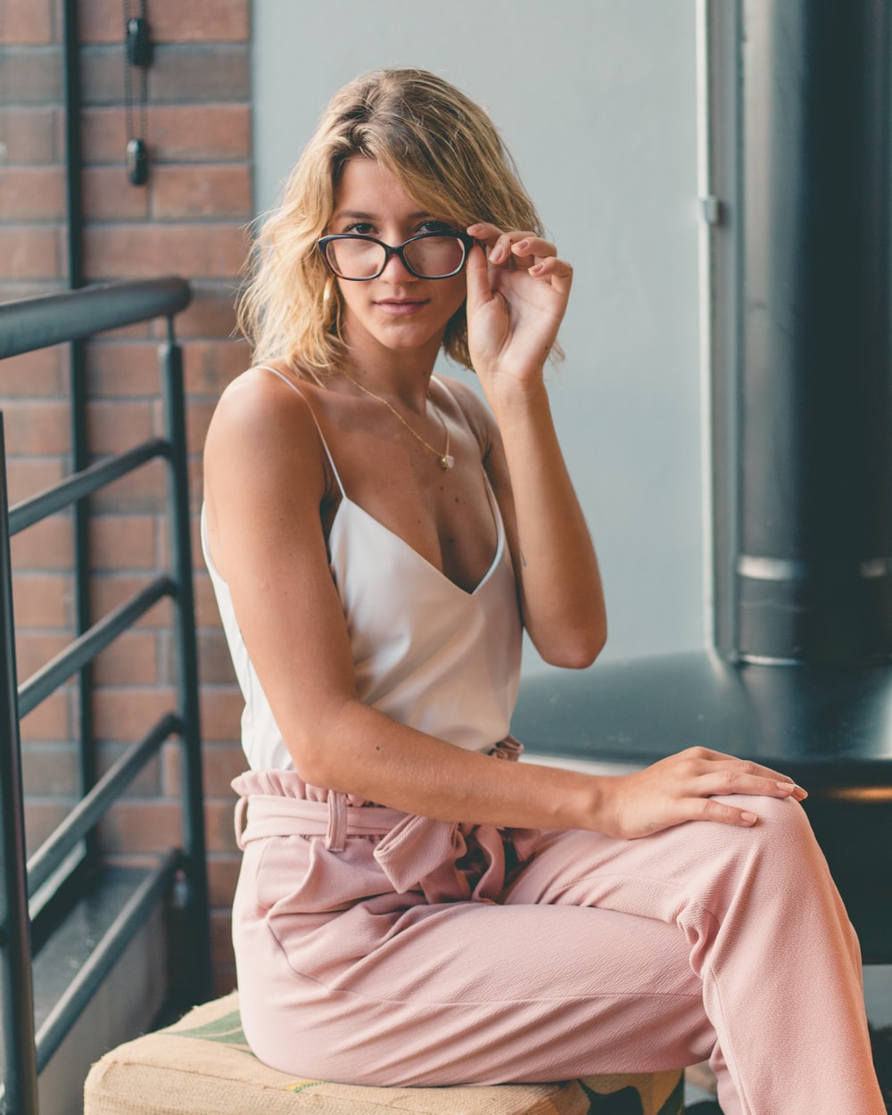 woman in eyeglasses,white spaghetti strap v-neck top and peach-colored drawstring pants