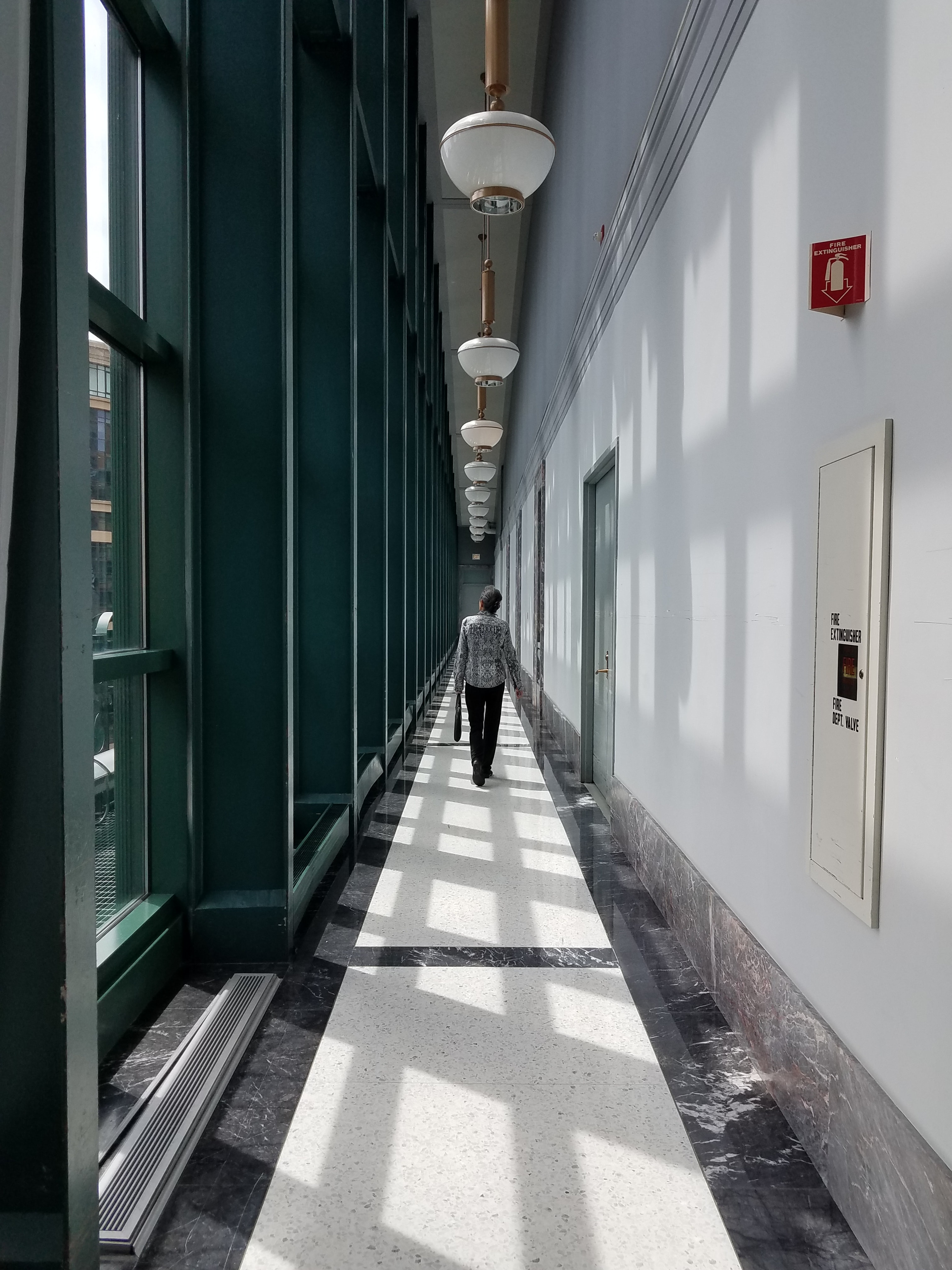 person walking on hallway with pendant lamps