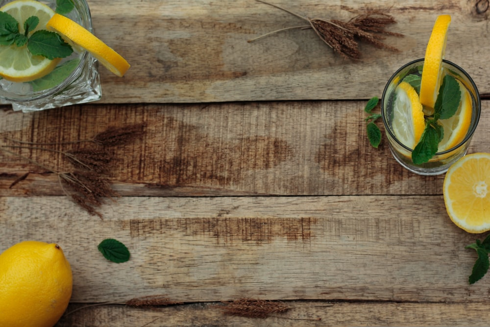 high angle photography of drinking glasses with slices of lemons on table