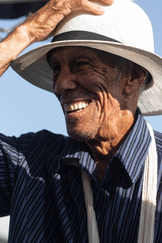 smiling man holds white hat