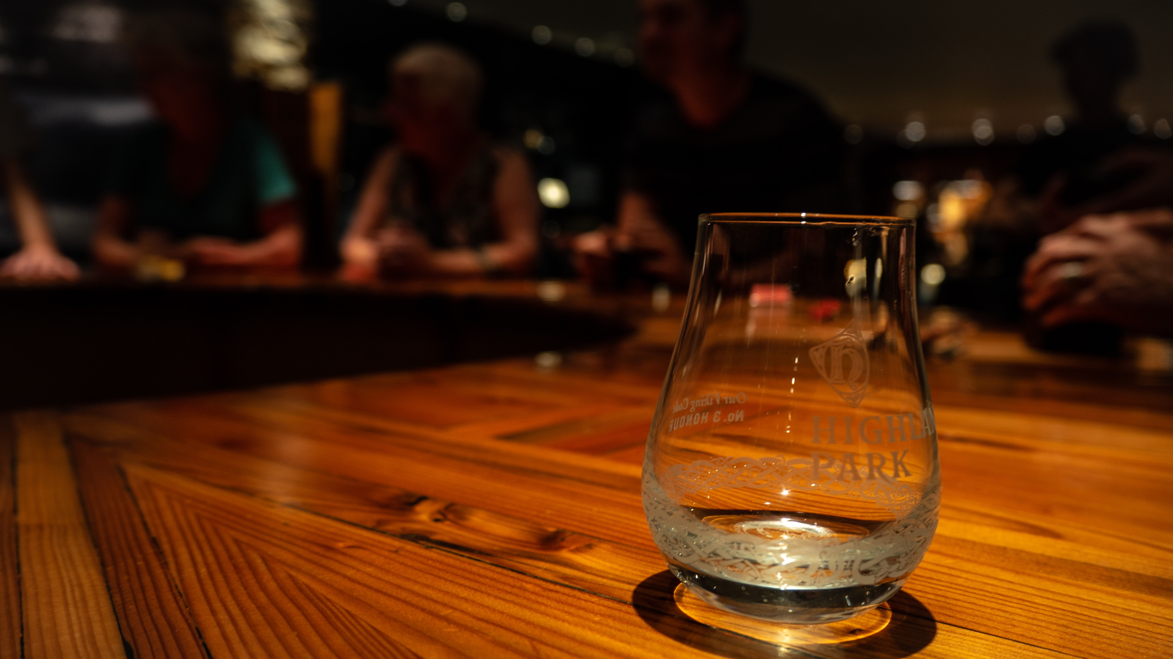 shallow focus photography of clear drinking glass on brown wooden table