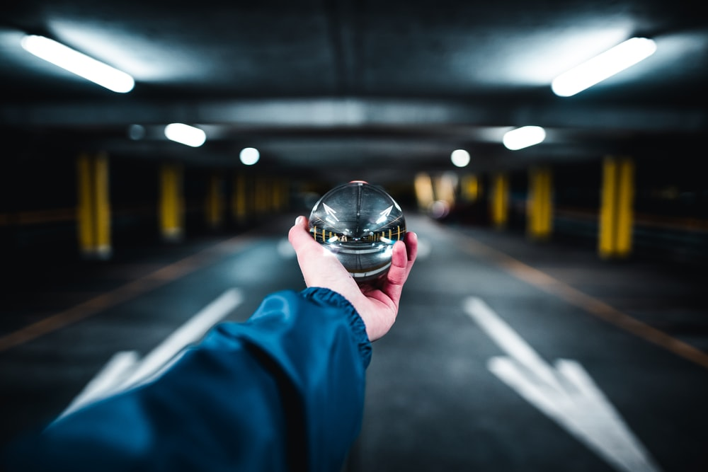 person holding grey glass ball