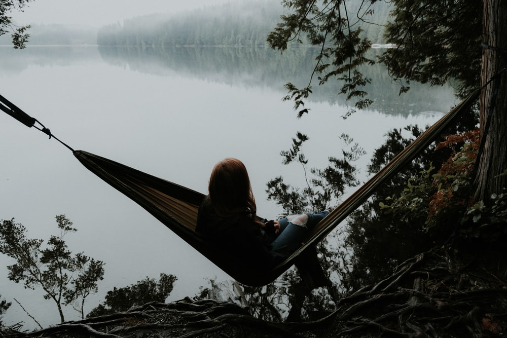 woman sitting on hammock while facing backwards