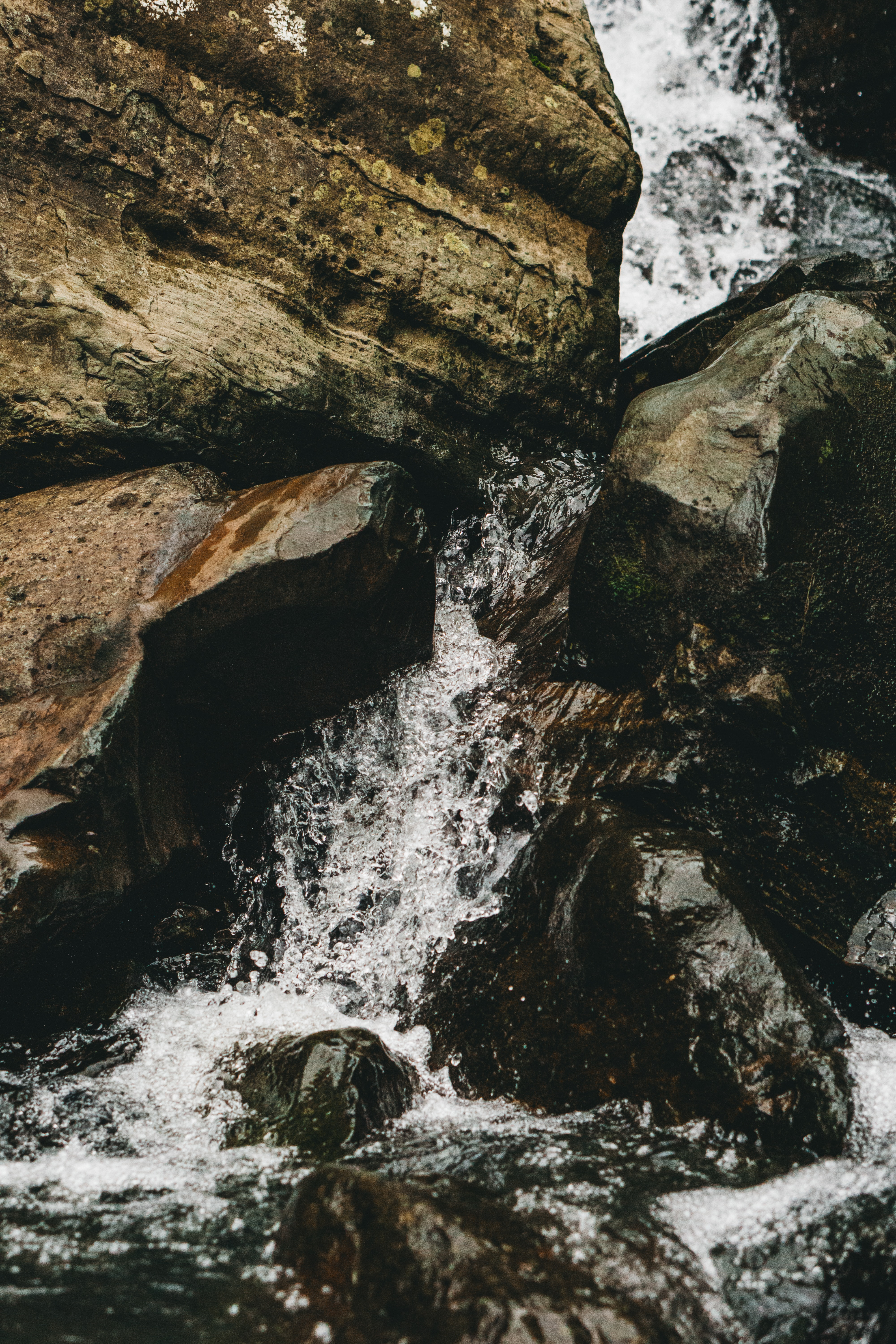 waterfalls in the middle of brown rocks