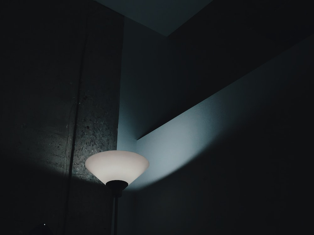 turned-on white and black floor lamp near wall in room
