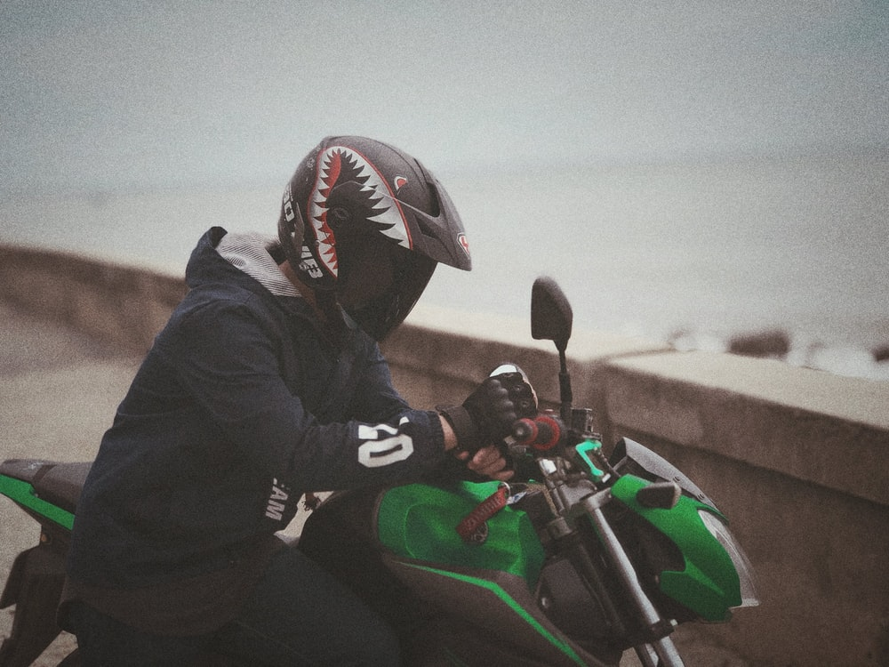 man beside green-and-black motorcycle