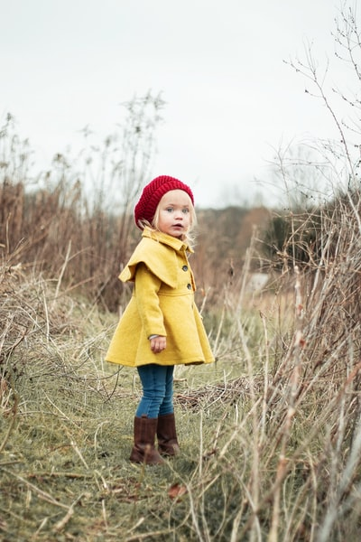girl wearing yellow coat standing on the grass field