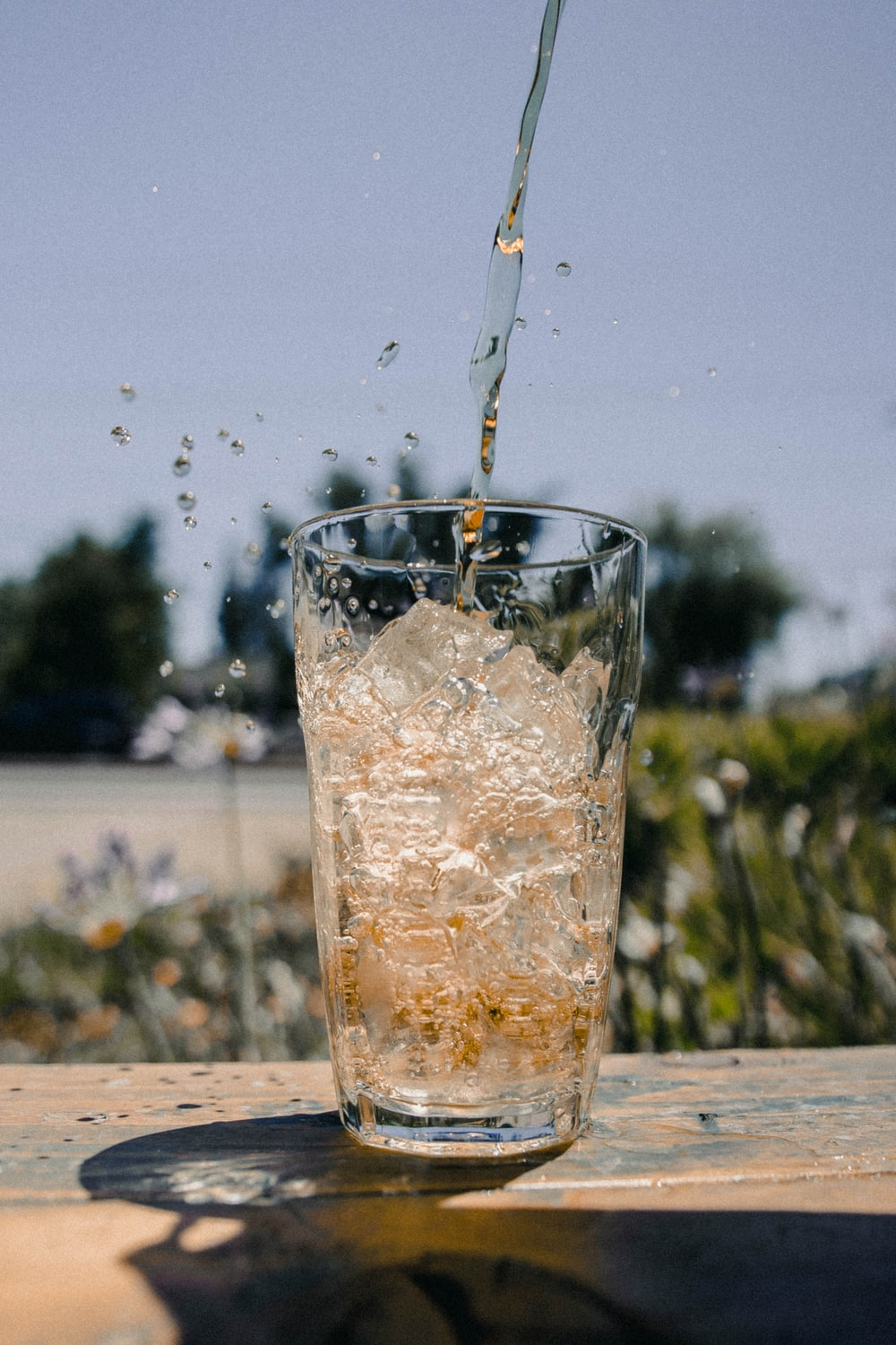 clear drinking glass with ice cubes and flowing liquid during daytime