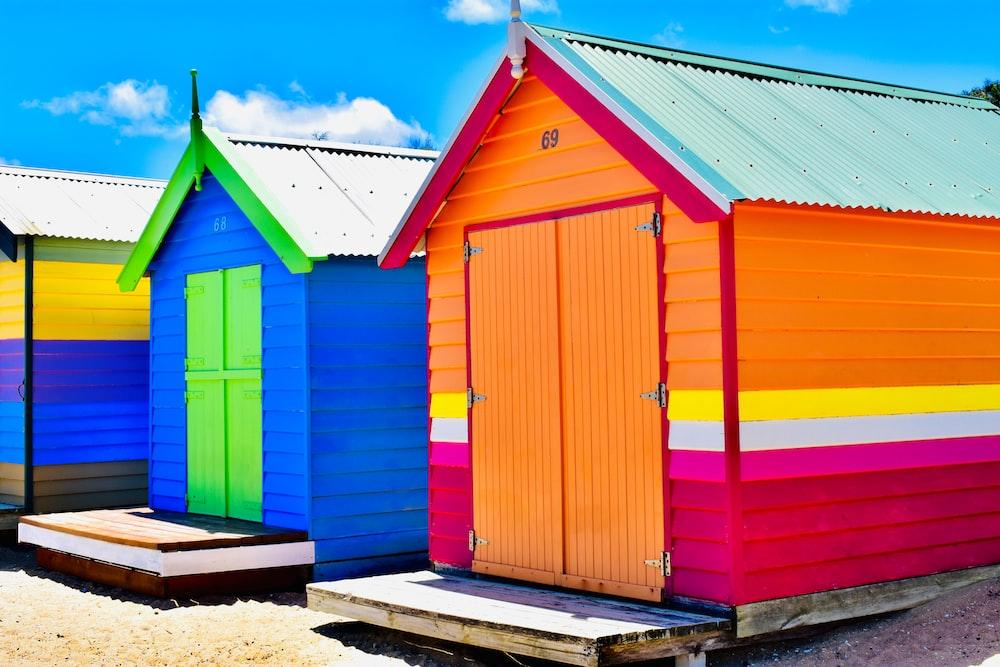 three assorted-color sheds under blue sky