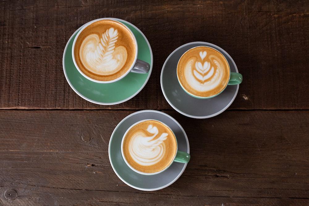three ceramic mugs with latte
