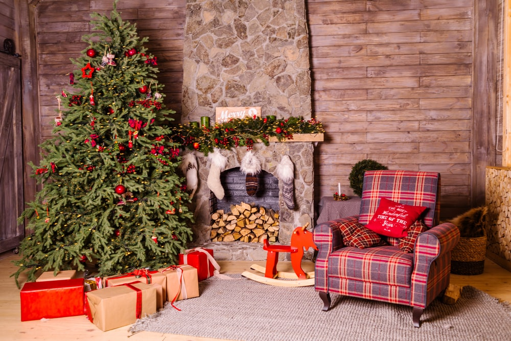 green Christmas tree beside brown and purple sofa chair