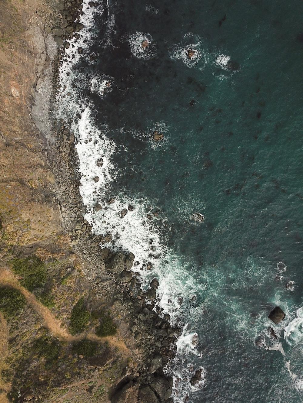 water smashing on rocks near cliff during daytime