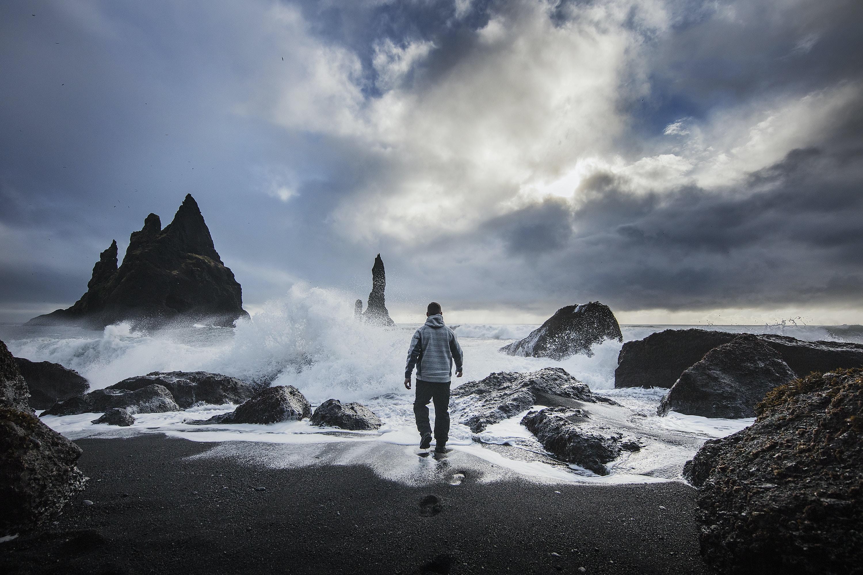 man standing beside beach under white cloudy sky