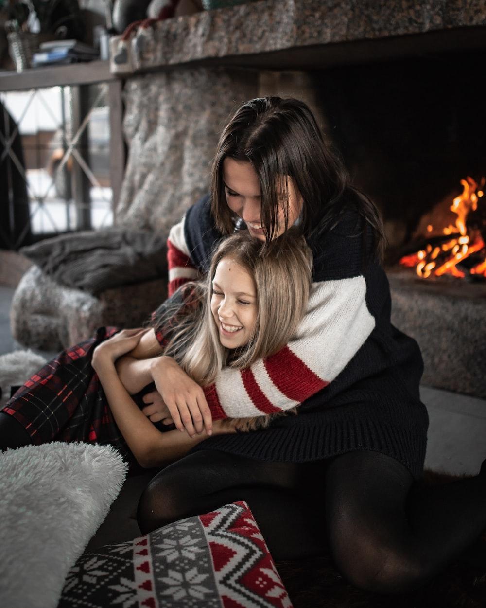 woman hugging girl while sitting near fireplace