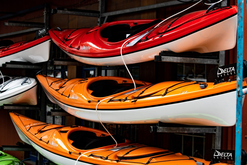 assorted color kayaks on shelf