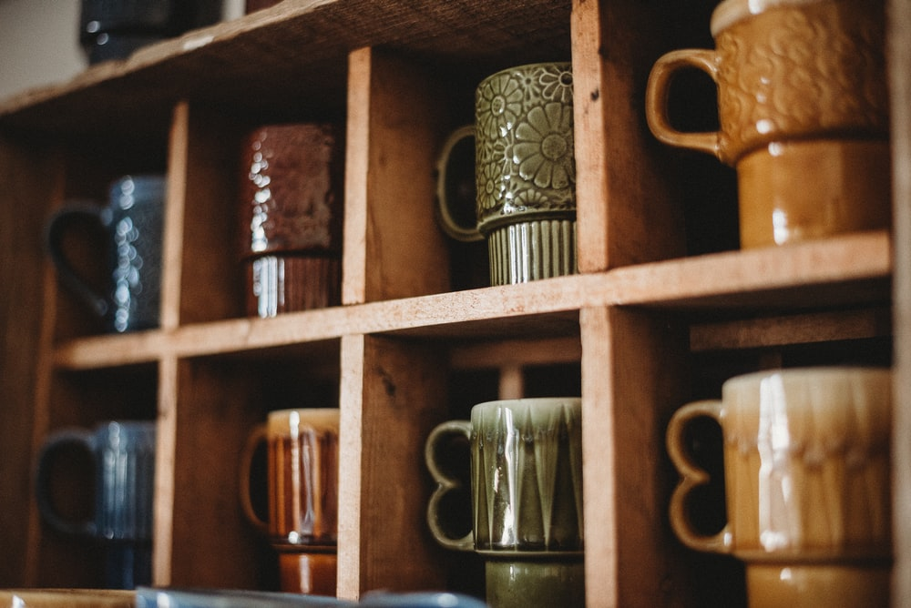 assorted-color ceramic mug on the shelf