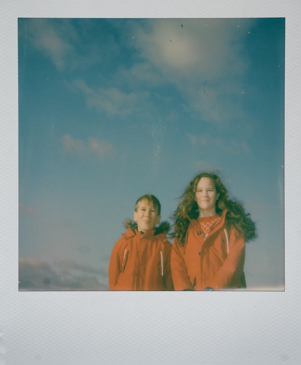 smiling boy and girl in orange jackets