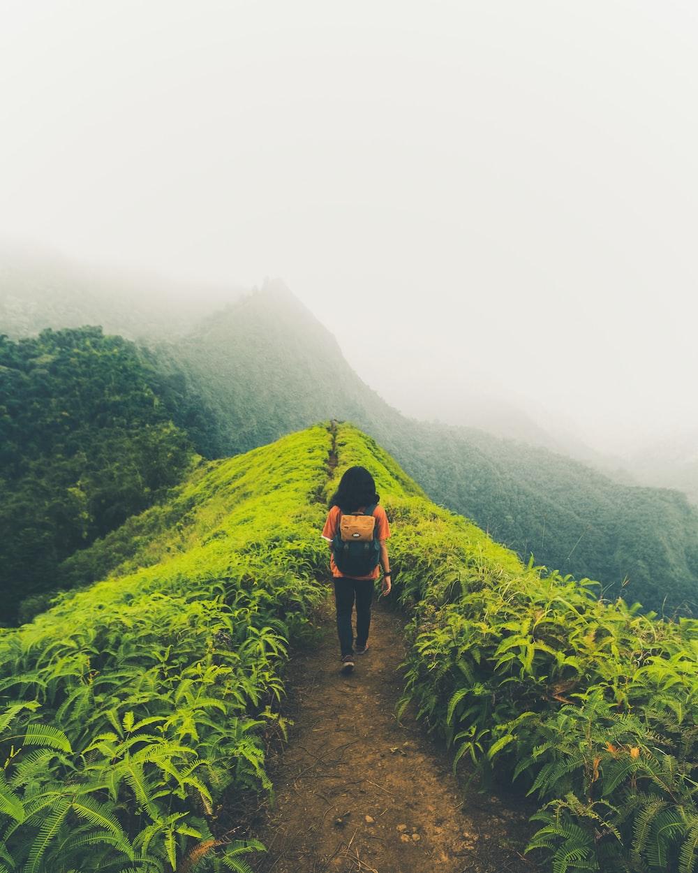 woman walking on mountain pathway