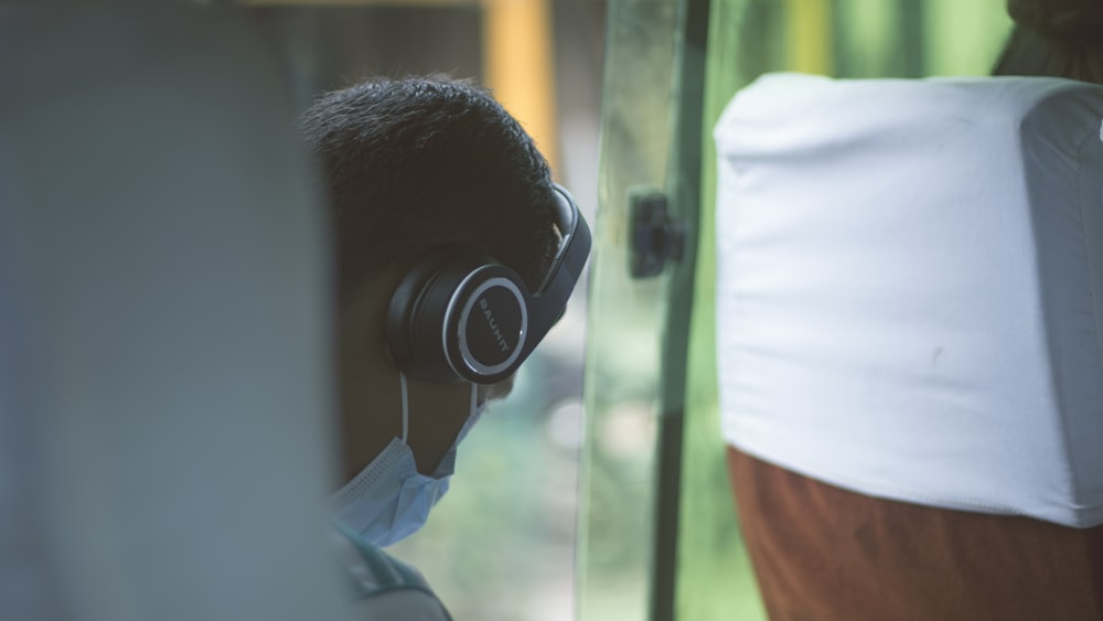 person wearing black wireless headphones and blue mask