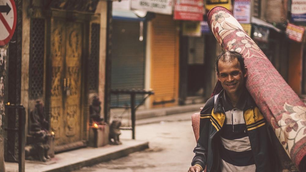 smiling man carrying carpet