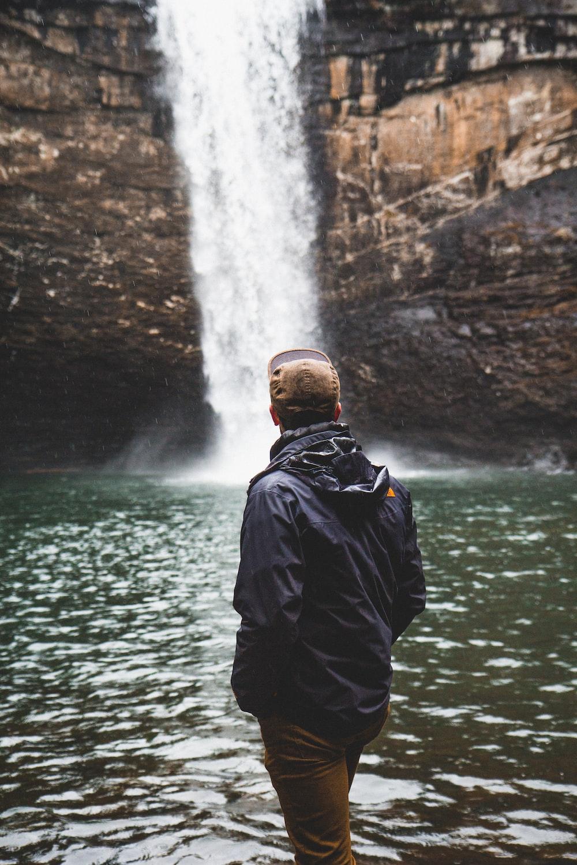 man wearing blue jacket standing near the waterfalls