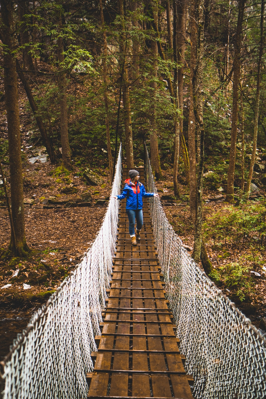 woman crossing brown bridge