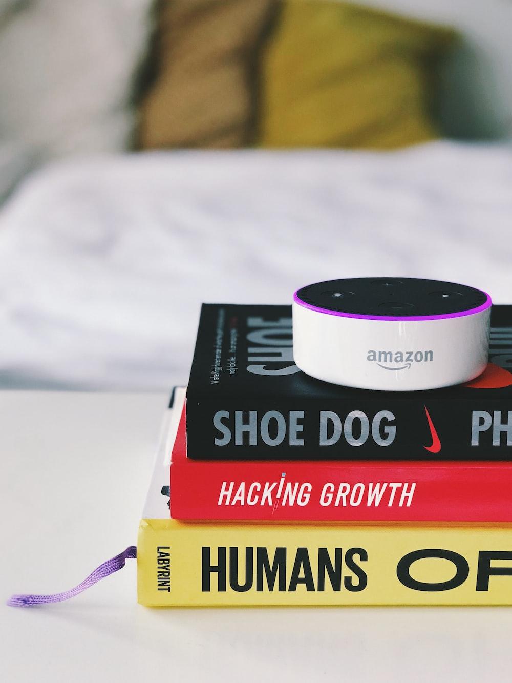 white Amazon Echo Dot speaker on book