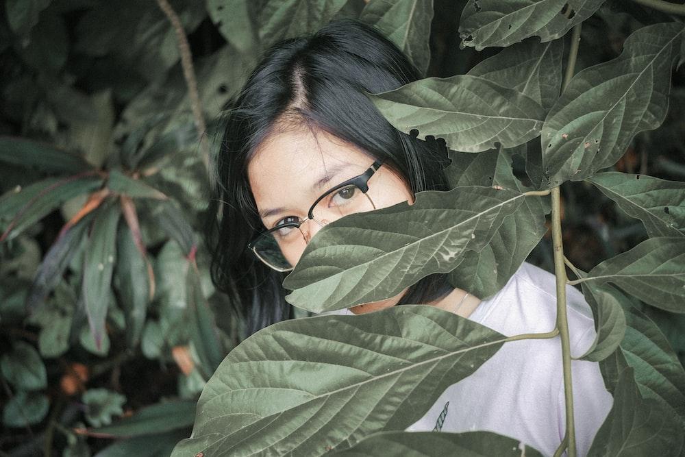 woman behind leaves