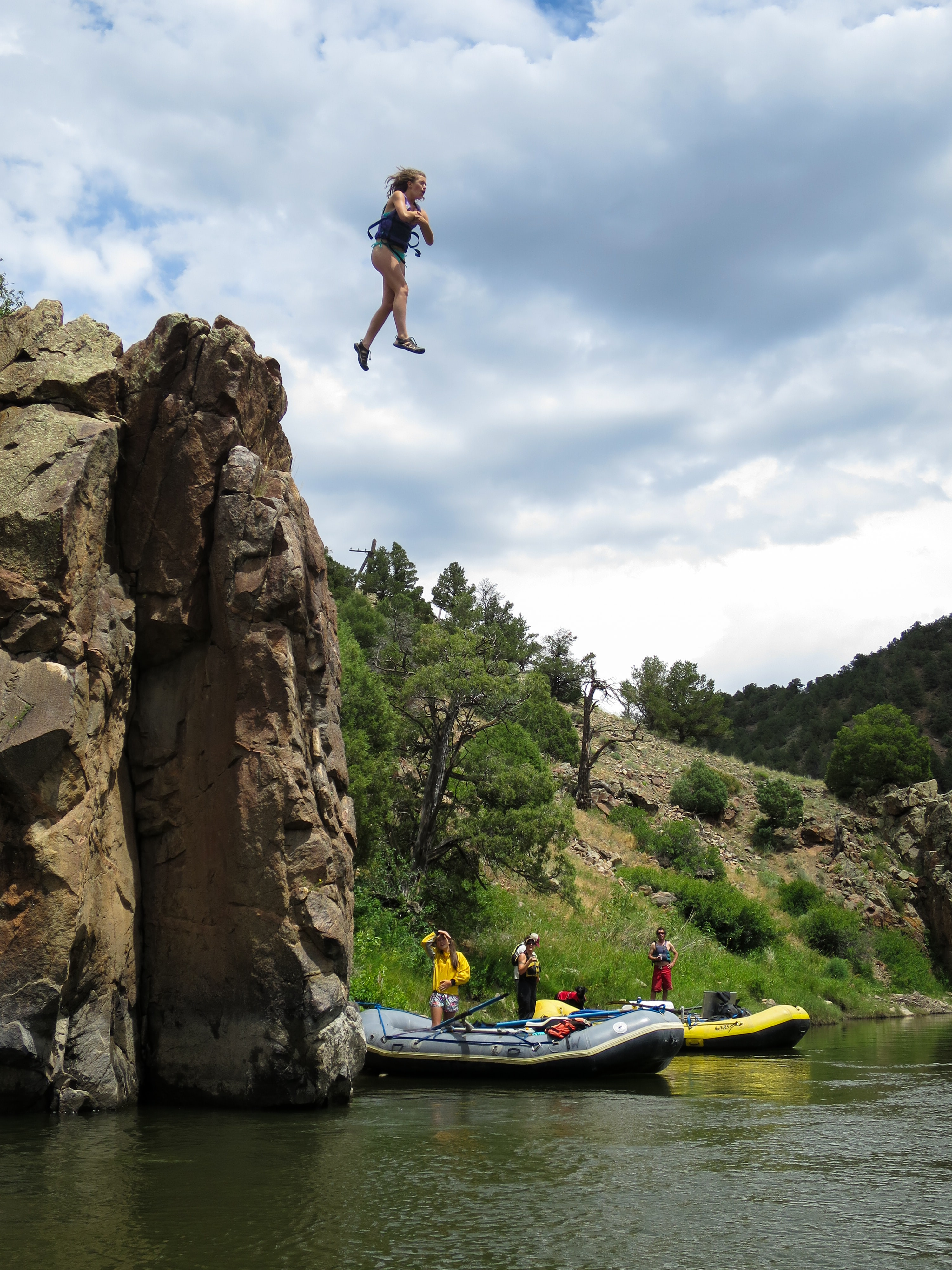 woman jumping from hill to body of water