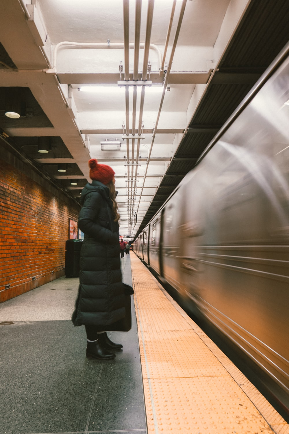 woman wearing bubble trench coat standing in front of train rail