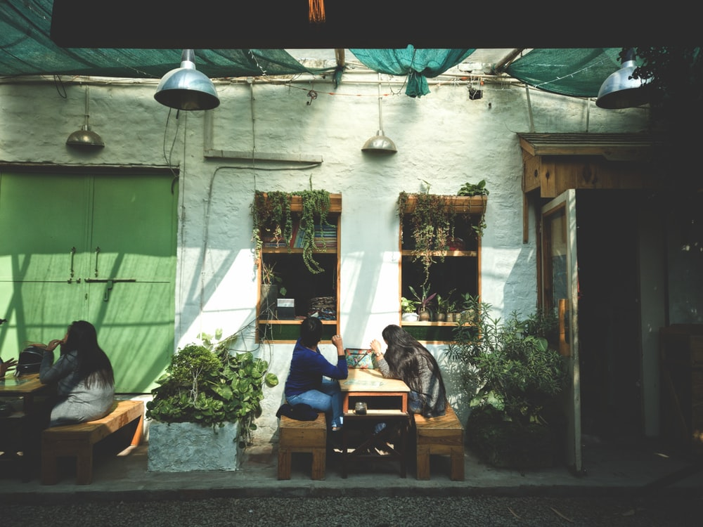 2 women sitting face to face on outdoor coffee shop
