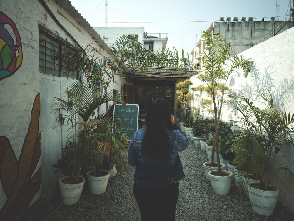 woman standing beside the house during daytime