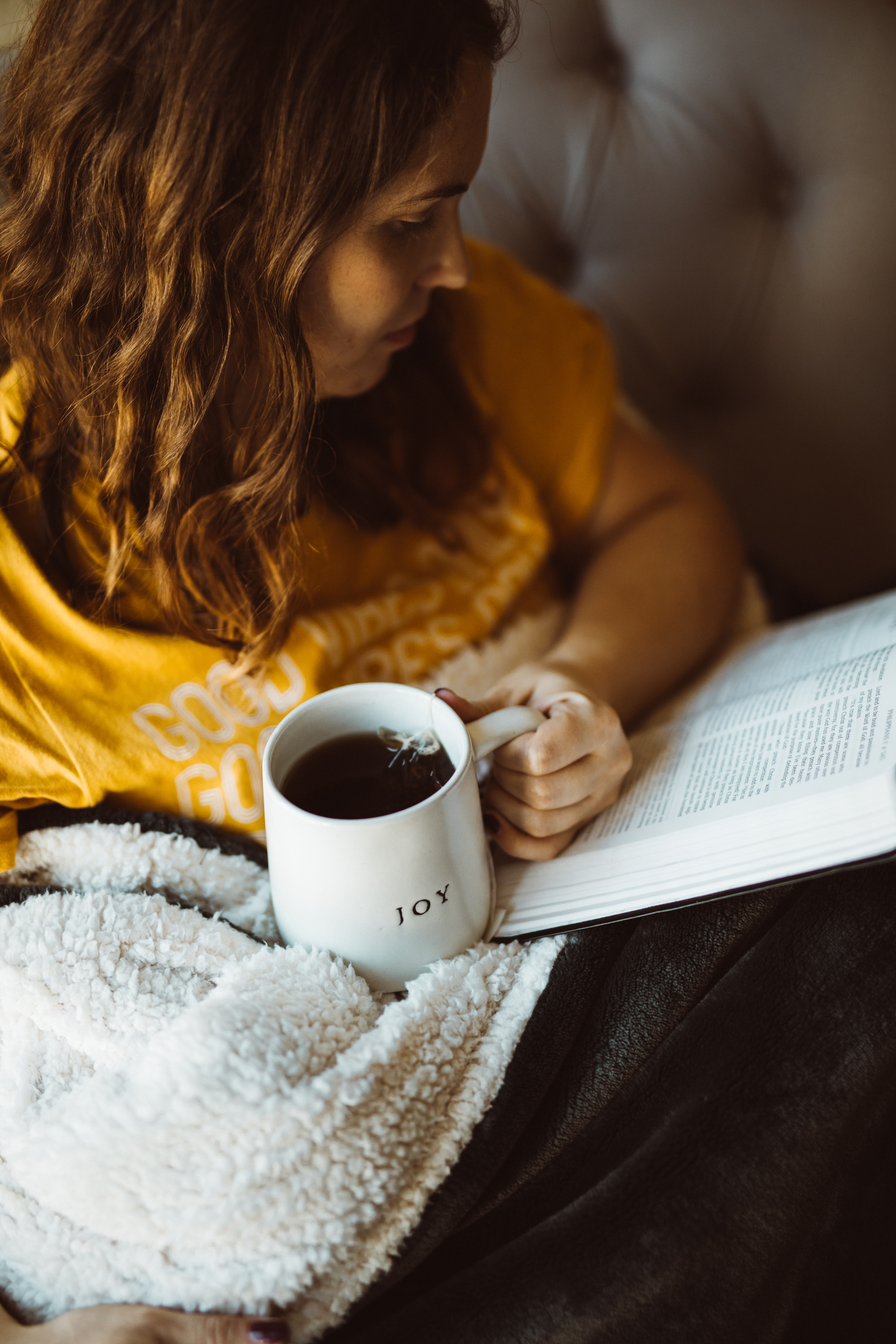 woman reading book while holding mug of coffee