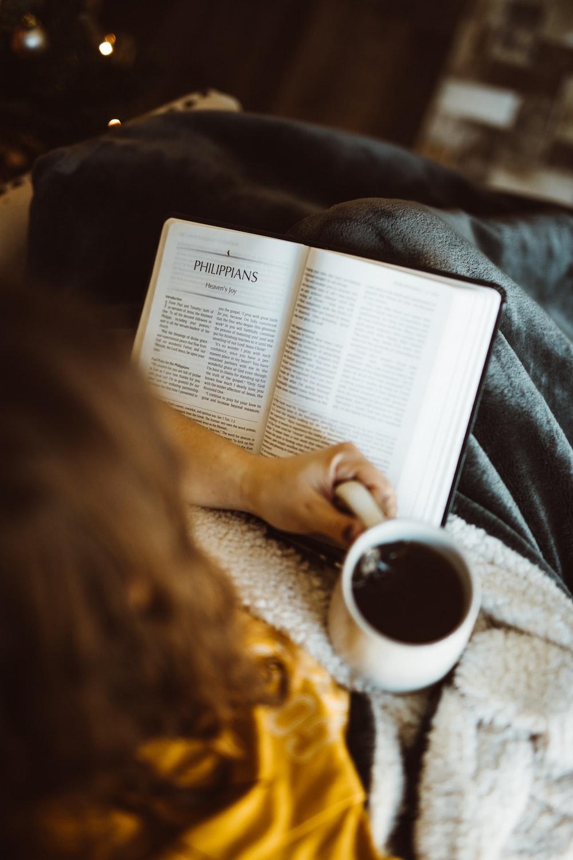 person holding white ceramic mug while reading book
