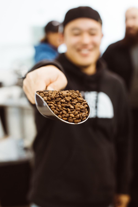 man in black hoodie shows scoop of coffee beans