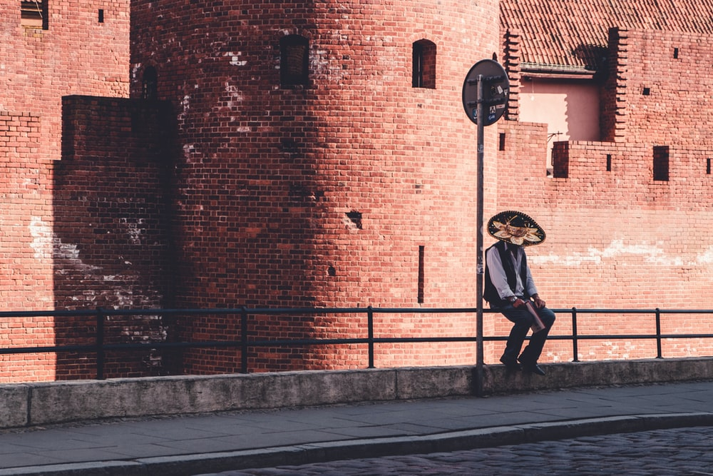 man sitting on metal rails