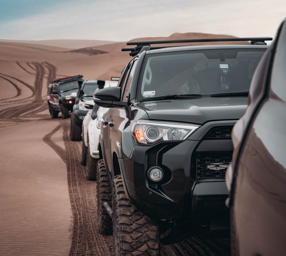 black SUV running on dune san