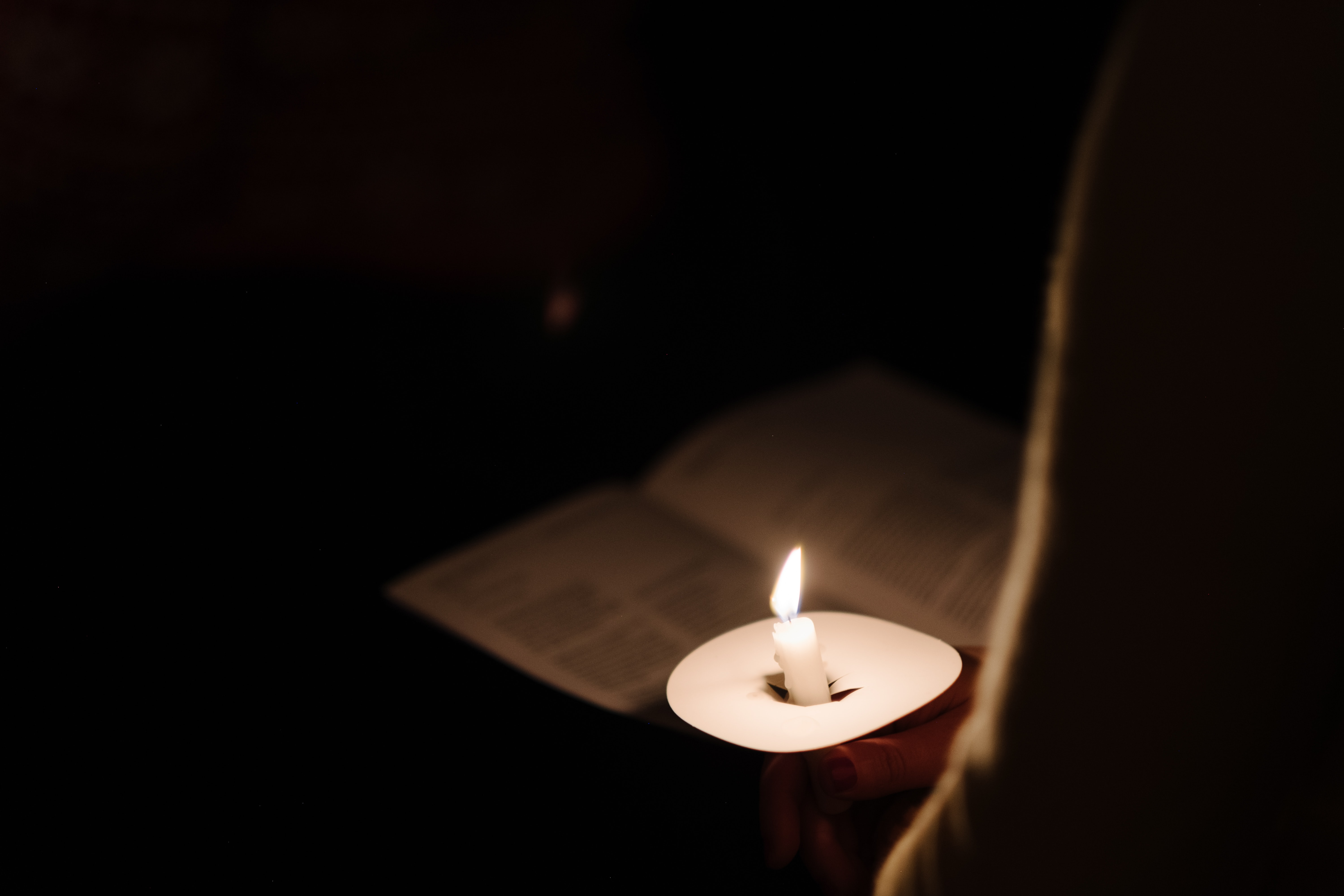 person holds lighted candle and paper