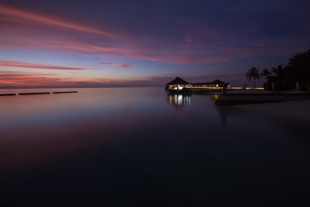 lighted gazebo across beach during pink sky sunset