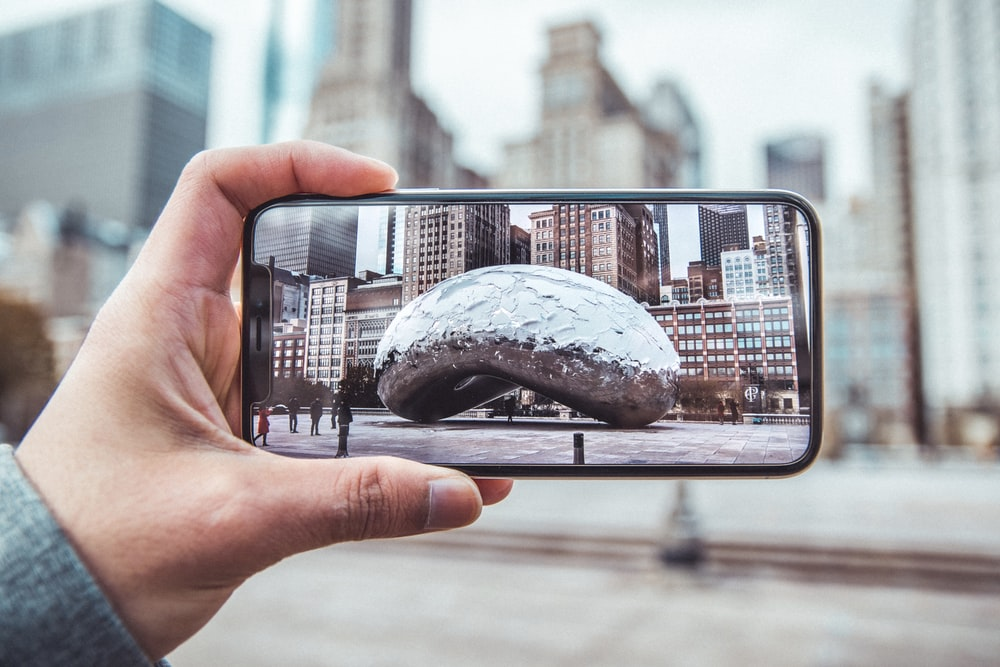 person holding smartphone showing compendium photo