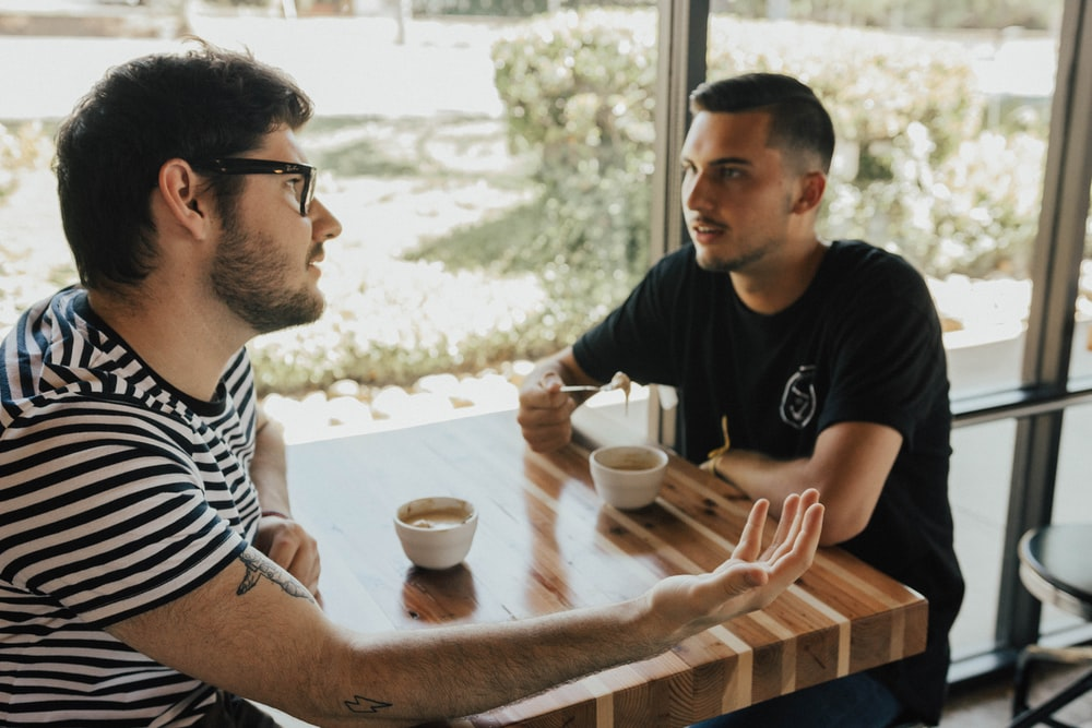 two men having conversation on table