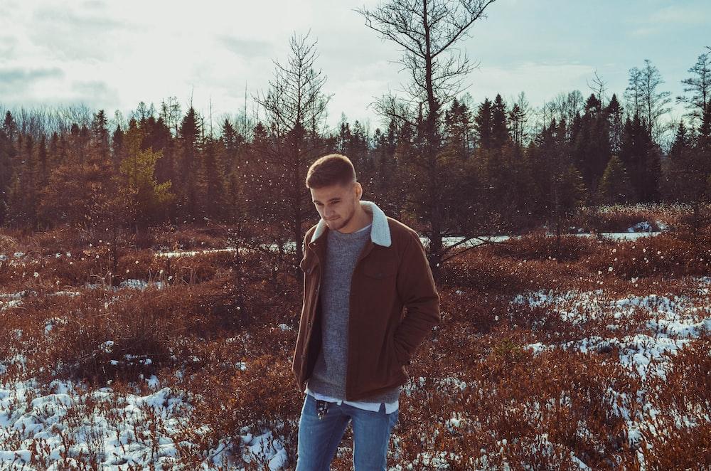 man wearing brown jacket standing on grass field