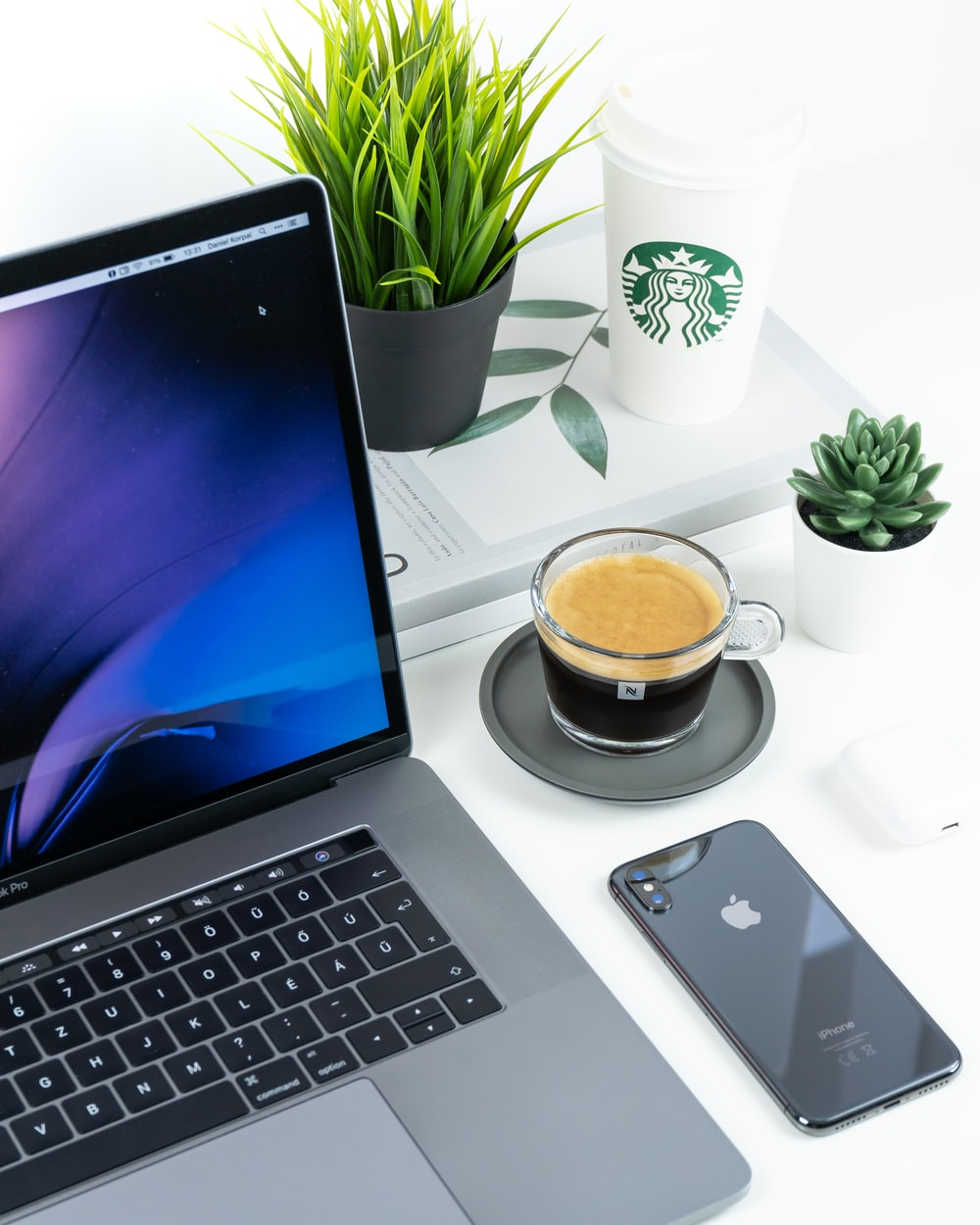 laptop beside iPhone and coffee in cup on table