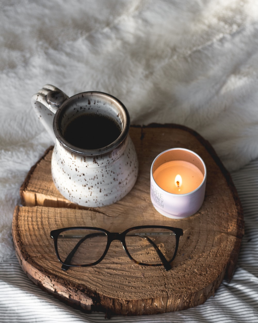 black-framed eyeglasses beside candle