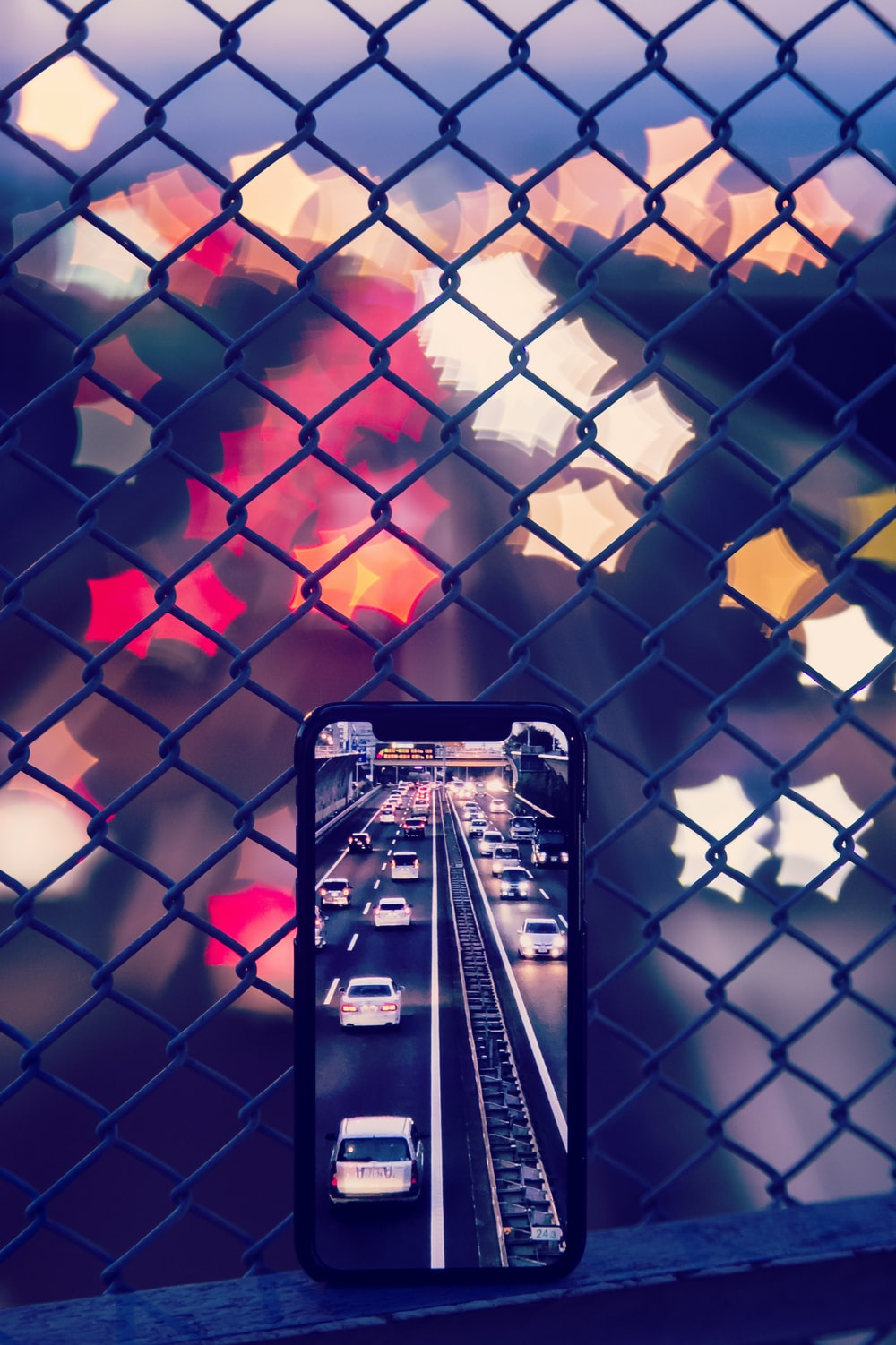 smartphone leaning on grey wired fence capturing vehicles on road