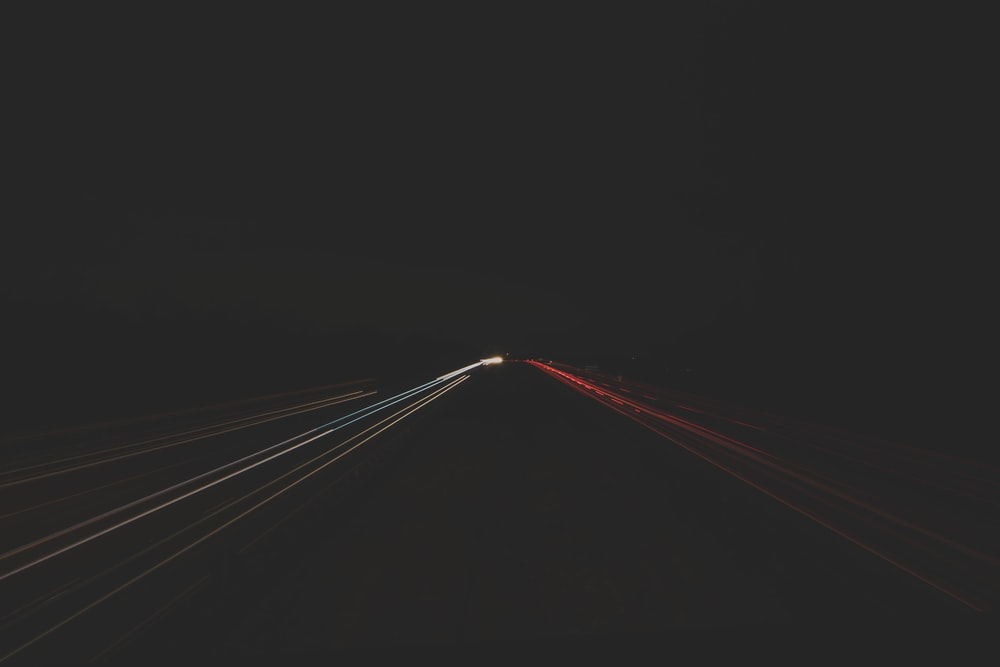 time lapse photography of passing cars on road