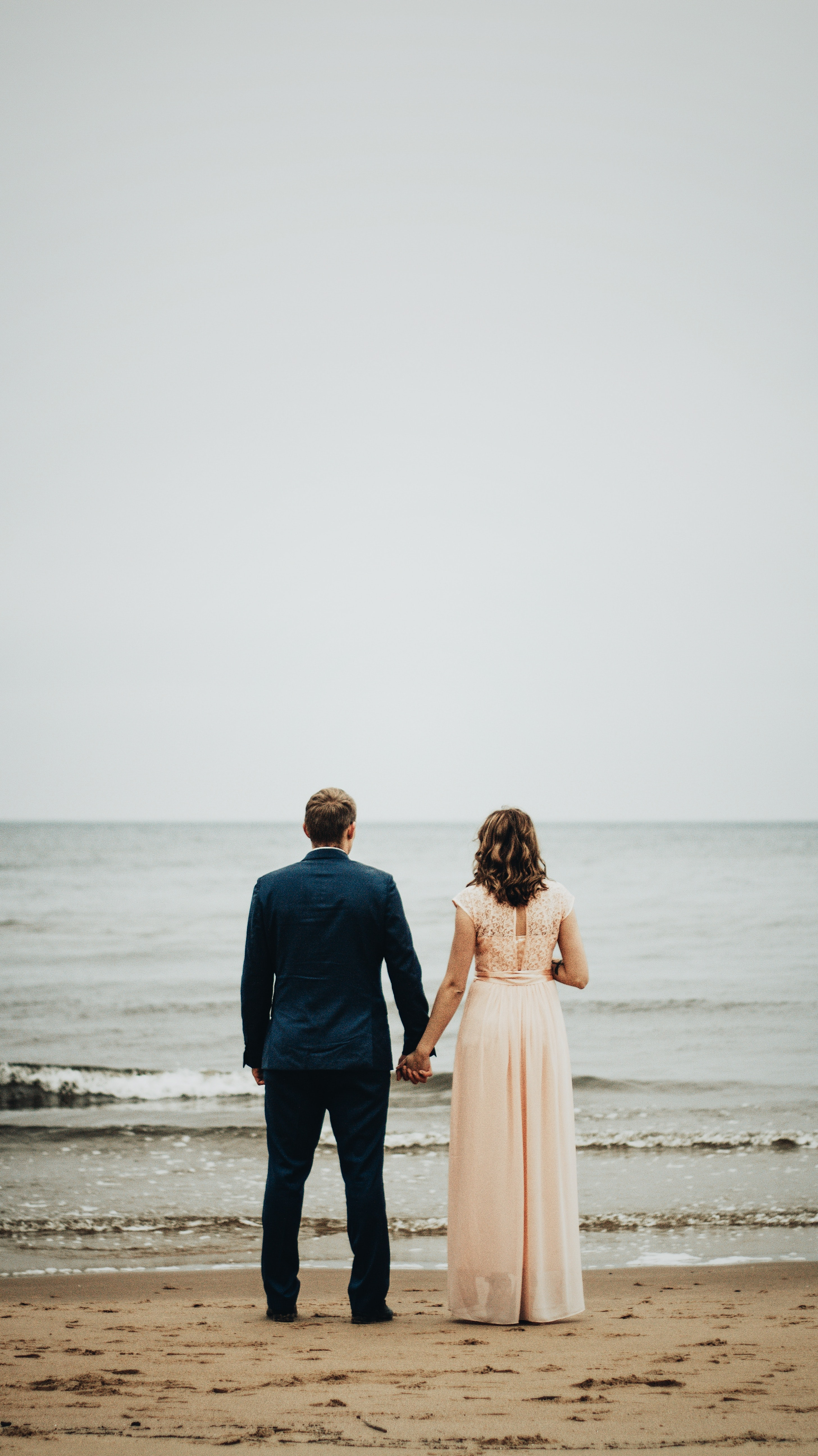 couple standing on seashore near sea