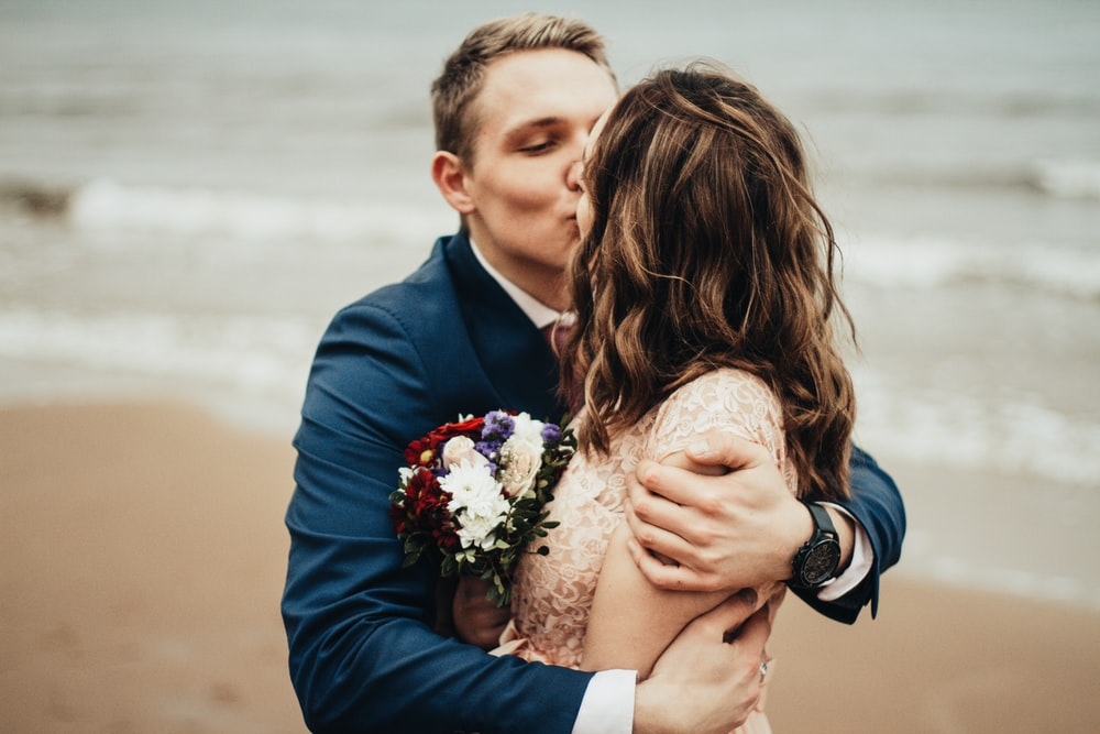 man and woman kissing at the beach during daytime
