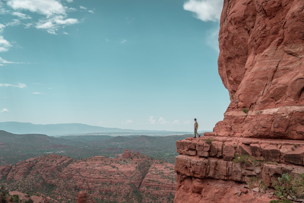 man standing on brown cliff
