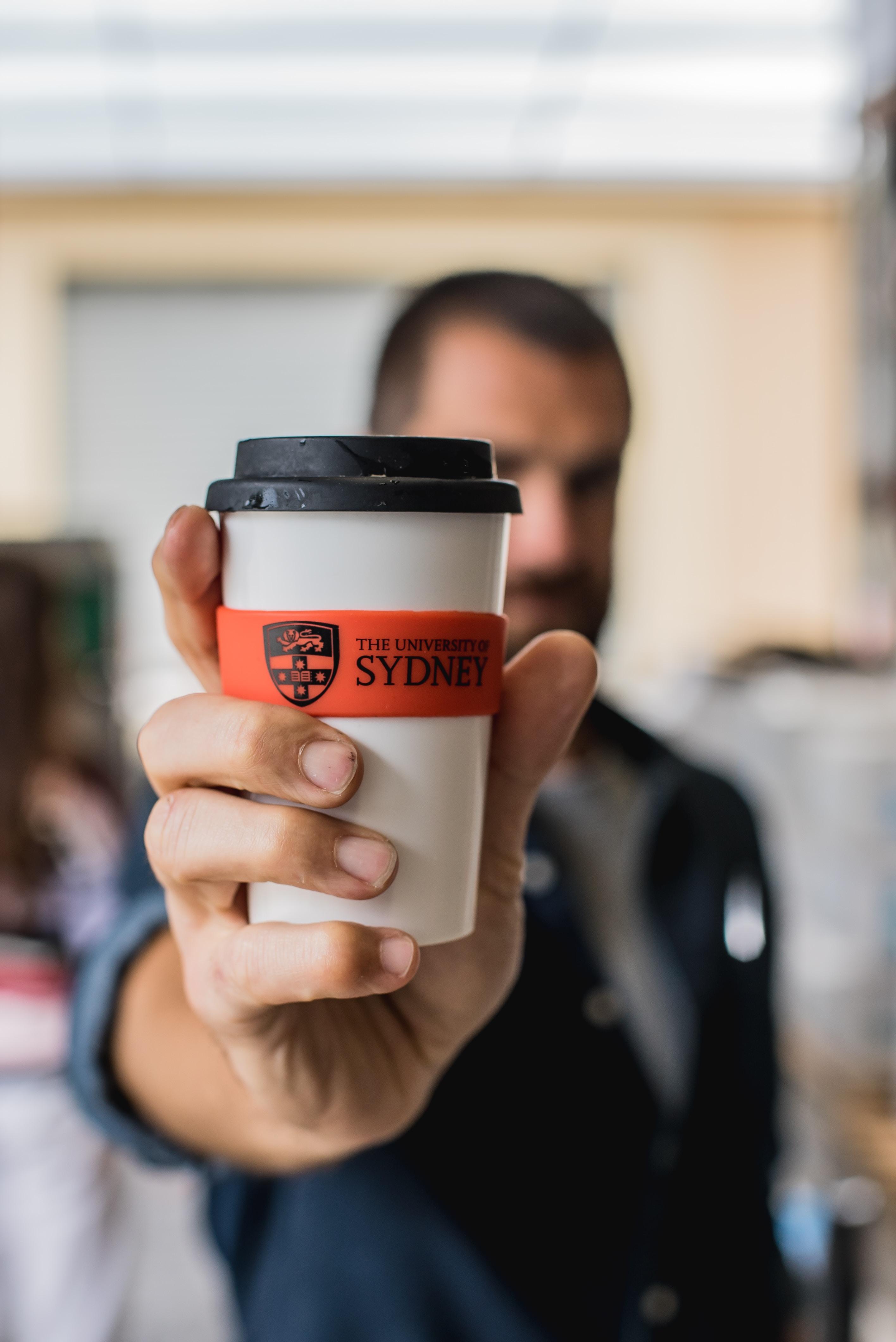 man holding sydney drinking cup